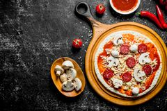 Preparation pizza. Rolled out dough with tomato paste, sausages, mushrooms and cheese. On rustic background stock photo