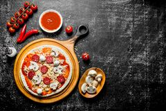 Preparation pizza. Rolled out dough with tomato paste, sausages, mushrooms and cheese. On rustic background royalty free stock images