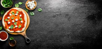 Preparation pizza. Rolled out dough with tomato paste, spinach and mozzarella. On black rustic background royalty free stock photography