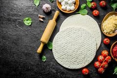 Preparation pizza. Round dough with tomatoes, cheese and spinach. On black rustic background royalty free stock photo