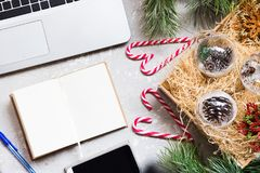 Laptop, phone, notebook, Christmas decorations - the concept of preparing for the holidays. View from above Royalty Free Stock Photo
