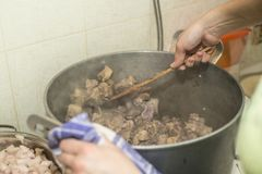 Preparation of pork meat for preservation closeup, stewing in a saucepan, mixing with a wooden spoon stock photo