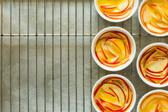 Preparation portioned apple cobbler in white bowls. On grey metal background. Top view stock image