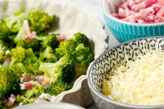 Preparation of quiche with broccoli, cheese and bacon. A preparation of quiche with broccoli, cheese and bacon Royalty Free Stock Images