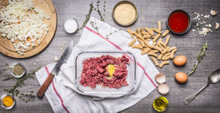 Preparation of raw minced meat balls with egg breadcrumbs eggs paste tomato sauce, garlic herb seasoning knife sliced onions Royalty Free Stock Image