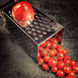 Preparation recipe tomato  juice. Large tomato and old grater down to small grape cherry tomatoes on retro vintage rustic gray sto Royalty Free Stock Photography