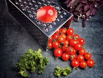 Preparation recipe tomato juice. Large tomato and old grater down to small grape cherry tomatoes on retro vintage rustic gray ston Stock Image