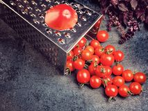 Preparation recipe tomato juice. Large tomato and old grater down to small grape cherry tomatoes on retro vintage rustic gray ston Royalty Free Stock Photography