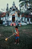 in preparation for a religious celebration two young boy is lighting up the candles around the theravada buddhist monastery stock photo