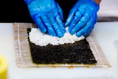 Preparation of rolls in a sushi bar. A professional cook wearing blue gloves is preparing traditional Japanese food. Rice, sea kale, cucumber stock image
