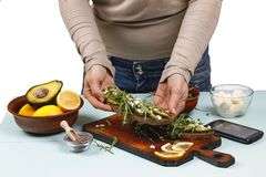 Preparation of sandwiches with arugula and avocado. Healthy food. A useful sandwich in the hands of a woman. Close up Stock Image