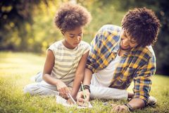 Preparation for school. African American father and daughter writing together in nature stock photo