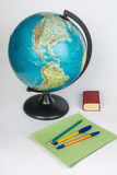 Preparation for school. Globe, pens, a dictionary and a stack of notebooks Royalty Free Stock Photo