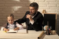 Preparation for school. Schoolgirl and her tutor with serious faces write in notebook Royalty Free Stock Photography