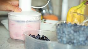 Preparation smoothie with strawberries and milk stock footage