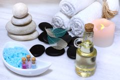 Preparation for the spa procedure, on a white marble table, there is an aromatic oil, stones and salt for massage, soft Stock Photo