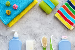 Preparation for spa therapy. Towels, soap, shampoo, lotion and brush on grey background top view copyspace Royalty Free Stock Photos