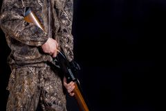 Preparation for spring or autumn hunting. Hunter in camouflage clothing with a gun on a black background isolated. The man with royalty free stock images