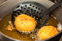 Preparation steps of traditional Colombian dish called stuffed potatoes. Deep frying stuffed pototoes royalty free stock image