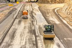 Steamroller doing road construction workPreparation of surface with water tank truck for asphalted royalty free stock photos