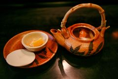 Chinese ceramic teapot for brewing and a cup with a slice of lemon, which stand on the table. stock images