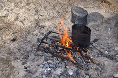 Preparation of tea on a fire in field conditions. Stock Photography