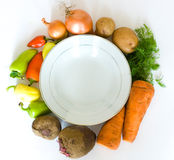 Preparation to dinner. Dish with vegenables around on a white background Royalty Free Stock Photos