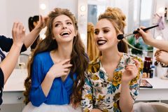Preparation to great party of joyful young women in hairdresser salon. Expressing true positive emotions, stylish look. Fashionable models, beautiful coiffure stock image