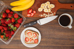 Preparation of toast with fruit and coffee. Slice of toast with fruit and cheese and some ingredients on a cutting board as seen from above. With some copy space Royalty Free Stock Photography
