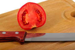 Preparation  Tomato. The tomato cut half-and-half and knife lay on a chopping board. Closeup. Isolated on a white background Royalty Free Stock Photo