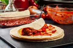 Preparation traditional mexican enchiladas with chicken meat, spicy tomato sauce and cheese Stock Photography