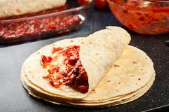 Preparation traditional mexican enchiladas with chicken meat, spicy tomato sauce and cheese Royalty Free Stock Photos