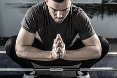Preparation before training in gym. Relaxed man with a beard sits on the floor above the chrome barbell bar in the gym. He holds his hands together. There are Stock Photo