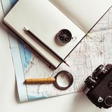 Preparation for travel. Map, notepad, camera, magnifier, compass, pencil and glasses. Vintage toned image Top view Flat lay Royalty Free Stock Image