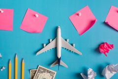 Preparation for Traveling concept, paper noted, airplane, money, passport, pencils, paper ball, push pin. Stock Photos