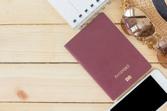 Preparation for Traveling concept, passport, smartphone, sunglasses, noted book, hat on a wooden background Stock Image