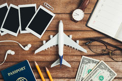 Preparation for Traveling concept, pencil, money, passport, airplane, watch, noted book, eyeglasses, ear phone, photo frame. Royalty Free Stock Photo