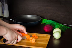 Preparation of Ukrainian soup - borsch. Cleaning and cutting potatoes carrots. Royalty Free Stock Photography