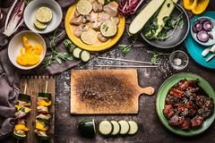 Preparation of various homemade meat vegetables skewers for grill or bbq on rustic background with ingredients. Plates, cutting board and kitchen tools, top royalty free stock photography