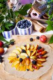 Preparation of whole-grain galette with plums, blackberries and. Preparation of whole-grain galette with plums on a white table. top view royalty free stock images