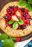 Whole-grain galette with plums and berries on dark background, t. Preparation of whole-grain galette with plums on a white table. top view royalty free stock image