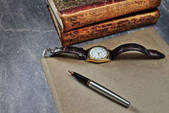 Preparation for writing of the letter. Still life with a sheet of paper, a fountain pen, hours and books in a retro style Royalty Free Stock Photography