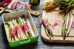Preparations for the asparagus wrapped in Parma ham casserole royalty free stock photos