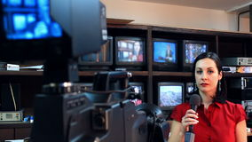 Preparations for the inclusion of live TV. Beautiful newscaster is preparing to publish the latest news, while the cameraman adjusts broadcasting equipment,video stock video footage