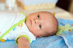 Preparations to bath. Five weeks thoughtful baby lying on bathing towel stock photography