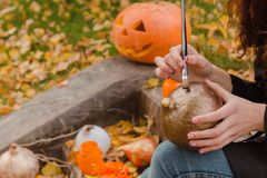 Woman`s hands draws on Halloween pumpkin Stock Photos