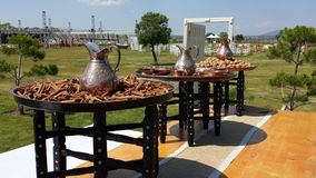 Preparations for Turkish weddings. Three round tables with metal pitchers, cinnamon and walnuts. On the grass seeded white furniture and built scene Stock Photo