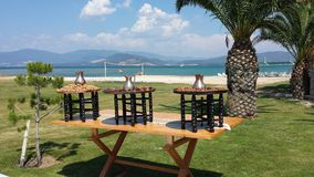 Preparations for Turkish weddings. Three round tables with metal pitchers, cinnamon, walnuts stands on the grass. In the background, beach, sea and palm trees Royalty Free Stock Photography