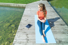 Preparations before yoga. Young sporty girl preparing for the yoga next to the water Stock Photos