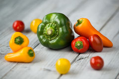 Preparato e pomodori ciliegia della paprica, mini peperoni dolci e peperone verde rossi, gialli ed arancio su un fondo di legno Immagine Stock Libera da Diritti